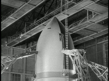 The totally unnecessary vertical construction of the spaceship in a specially built hangar is the same in the film and the Apollo Missions.
